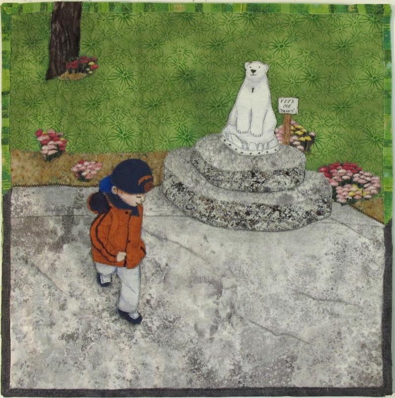 A litle boy runs past a statue of a polar bear.