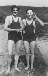 Two men in vintage bathing suits standing on a beach.
