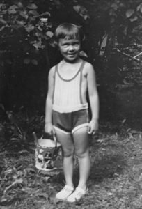 A little girl in a sunsuit holding a sand pail.