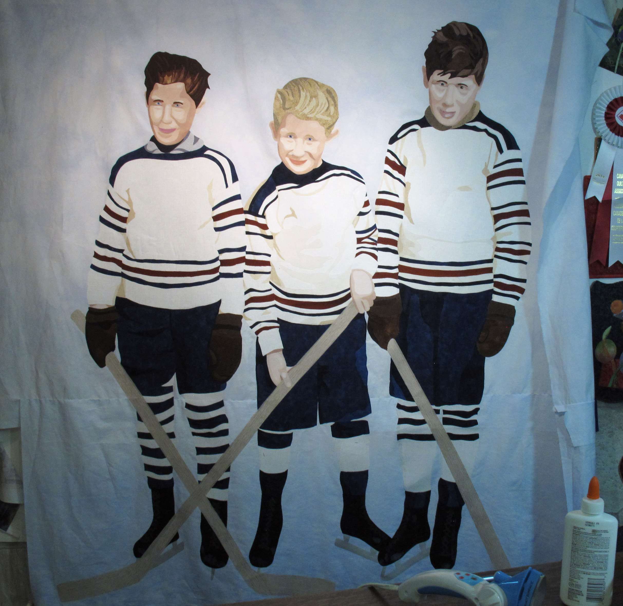 Three boys in hockey uniforms standing straight. Mistake corrected.