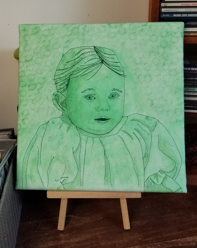 This portrait is of a baby stitched on fabric.
